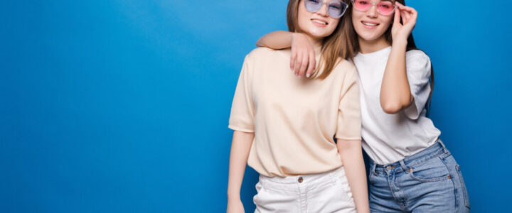 friends-forever-two-cute-lovely-girl-friends-sunglasses-posing-with-smile-isolated-blue-wall