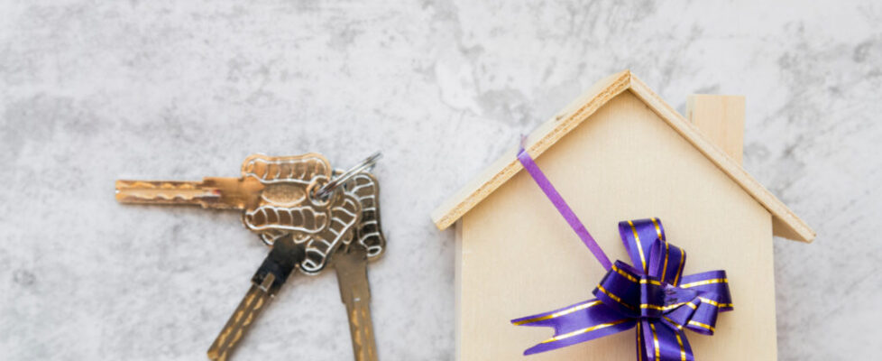 silver-keys-near-house-wooden-model-with-ribbon-bow-white-concrete-wall